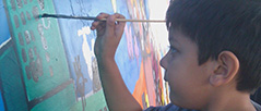 Boy painting a mural for Phoenix Festival of the Arts.
