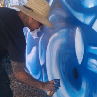 Angel Diaz painting the Phoenix Festival of the Arts mural