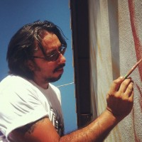 Hugo Medina painting the Phoenix Festival of the Arts mural