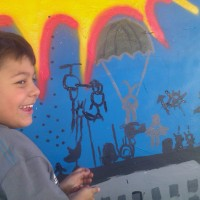 A young boy painting the Phoenix Festival of the Arts mural