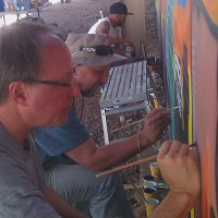 A Phoenix community member painting the Phoenix Festival of the Arts mural