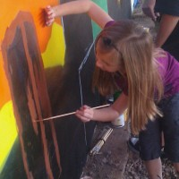 A young girl painting the Phoenix Festival of the Arts mural