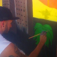 A community member helping with the Phoenix Festival of the Arts mural
