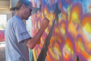 A Phoenix community member working on the Phoenix Festival of the Arts mural